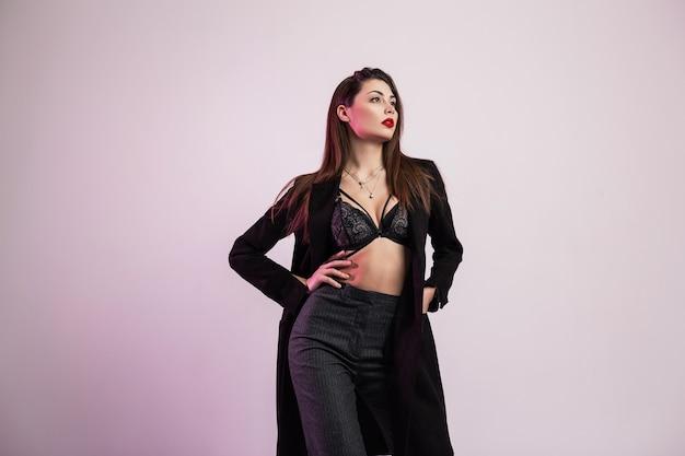Eleganza sexy giovane donna in un cappotto lungo alla moda in biancheria intima alla moda in pantaloni alla moda con capelli castani chic con labbra rosse gonfie in posa in studio vicino al muro. modello di moda ragazza sensuale.