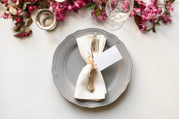 Regolazione della tavola di eleganza con i fiori di fioritura della mela sulla tavola bianca.