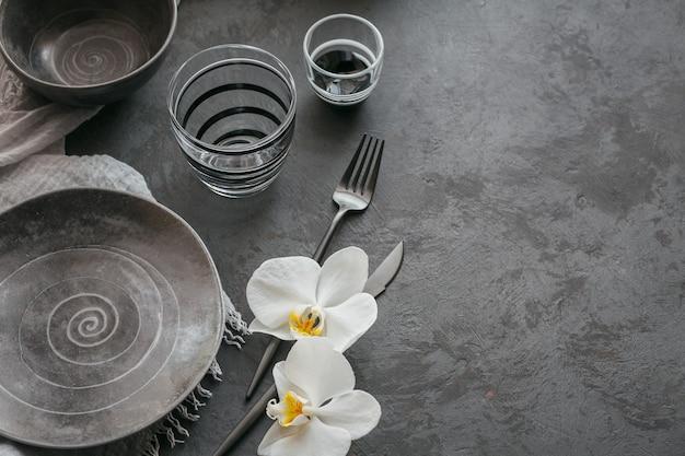 Tavola di eleganza con tovagliolo grigio lavorato a maglia, posate, piatti in ceramica, bicchieri e fiori di orchidea bianca sul tavolo scuro. decorazione della tavola moderna per le vacanze. cena romantica.