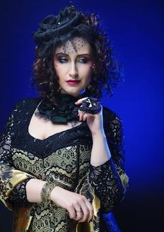 Donna di eleganza con trucco luminoso. foto di carnevale.