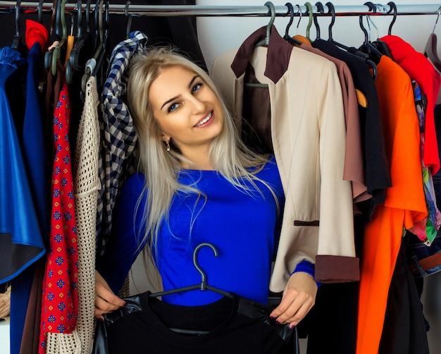 Giovane donna bionda di eleganza nel negozio di vestiti che sorride sulla parte anteriore