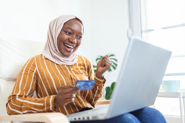 Elegante e attraente donna musulmana che utilizza un laptop mobile alla ricerca di informazioni sullo shopping online nel soggiorno di casa. ritratto di donna felice che acquista il prodotto tramite lo shopping online. paga con carta di credito