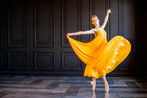 Un'elegante ballerina in scarpe da punta balla con un tessuto giallo fluente su uno sfondo grigio scuro