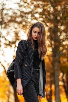 Elegante bella donna d'affari con labbra rosse in un abito nero alla moda con blazer e zaino in pelle cammina in un parco con fogliame autunnale giallo