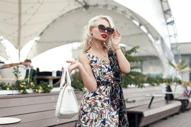 Elegante bella donna modello con occhiali da sole in un abito vintage di moda con un motivo con una borsa alla moda in città