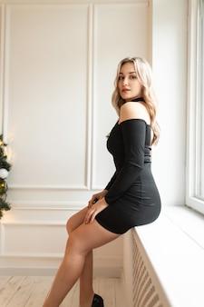 Elegante bella giovane donna sexy in un vestito nero con belle gambe si siede vicino alla finestra su uno sfondo bianco
