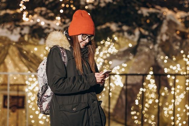 Bella donna elegante che manda un sms sullo smartphone nella città