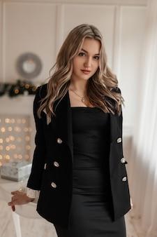 Bella ragazza elegante in un vestito nero alla moda con un blazer in una stanza contro uno sfondo di luci gialle