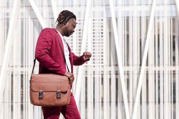 Elegante uomo d'affari nero con valigetta cammina attraverso il centro finanziario della città guardando l'orologio, copia spazio per il testo