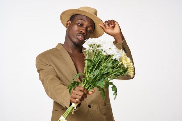 Elegante uomo di colore con bouquet di fiori