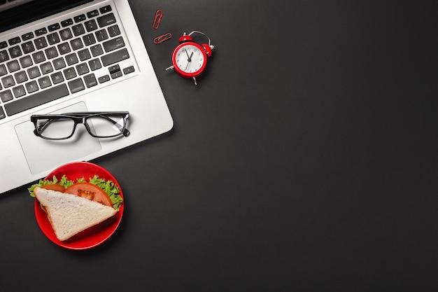 Elegante desktop da ufficio nero con laptop, tazza di caffè e un panino per pranzo. vista dall'alto con copia spazio