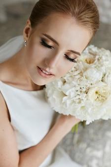 Ragazza di modello bionda elegante con trucco luminoso di nozze che posa con gli occhi chiusi e mazzo di fiori