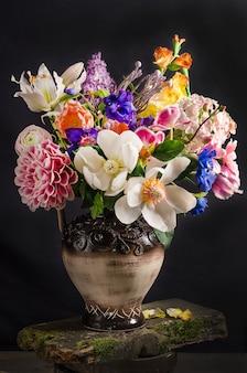 Elegante bouquet di fiori in un vaso su uno spazio nero in stile scuro, natura morta floreale
