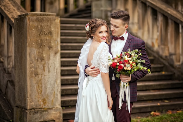 Sposa e sposo eleganti che propongono insieme all'aperto su un giorno delle nozze
