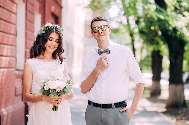 Elegante sposa e sposo che propongono insieme all'aperto in un giorno di nozze
