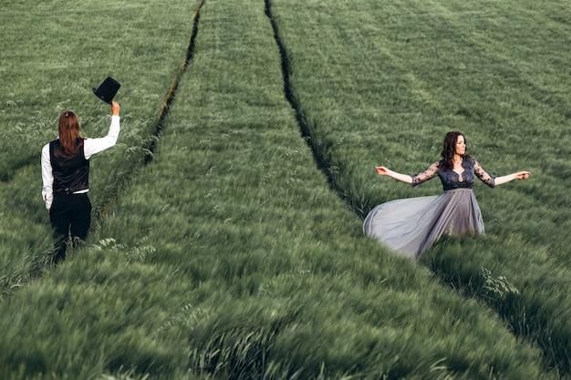 Sposa e sposo eleganti che camminano e che posano sul campo verde