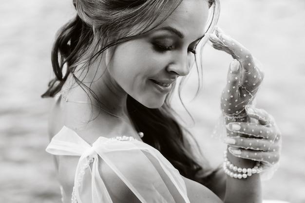 Un'elegante sposa in abito bianco, guanti e piedi nudi è seduta vicino a una cascata nel parco godendosi la natura. un modello in abito da sposa e guanti in un parco naturale. bielorussia. foto in bianco e nero