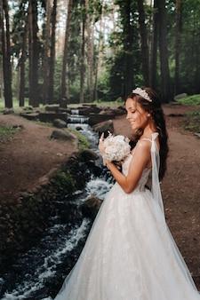 Una sposa elegante in abito bianco e guanti in possesso di un bouquet si trova vicino a un ruscello nella foresta, godendosi la natura.un modello in abito da sposa e guanti in un parco naturale.