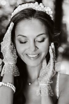 Una sposa elegante in abito bianco, guanti con un bouquet su una cascata nel parco, godendosi la natura. modello in abito da sposa e guanti nella foresta. bielorussia