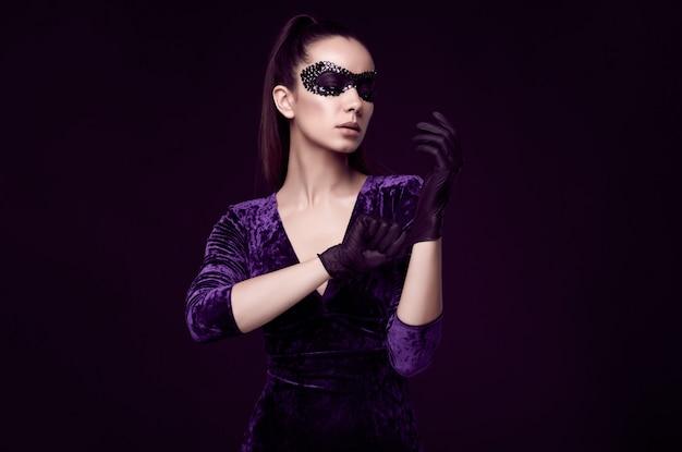 Elegante donna bruna in un bellissimo vestito viola e paillettes maschera guanto in su