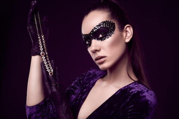 Elegante donna bruna in maschera di paillettes con guanti neri guarda la collana di diamanti