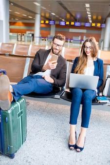 Elegante coppia di affari che lavora con laptop e telefono seduti nella sala d'attesa dell'aeroporto. concetto di viaggio d'affari