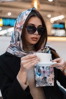 Elegante giovane donna d'affari in occhiali da sole alla moda in un elegante scialle di seta gode di un caffè in un caffè. la bella modella moderna della ragazza beve il cappuccino saporito caldo all'interno.