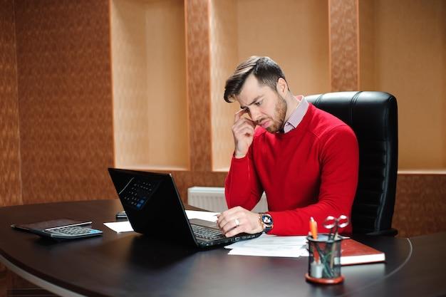 Uomo d'affari elegante che analizza i dati in ufficio nello sforzo.