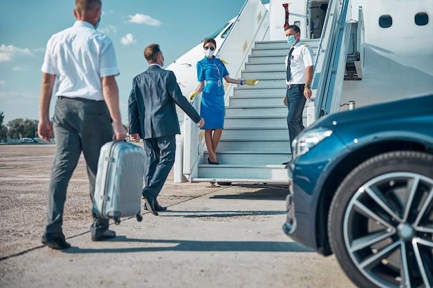 Elegante uomo d'affari e assistente con valigia che indossa maschere sterili durante il trasferimento in aereo e il boarging