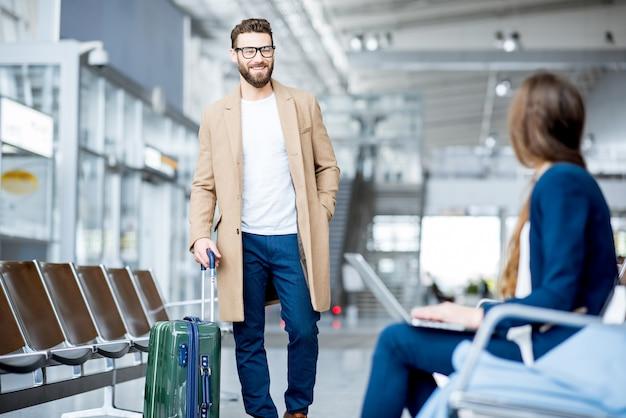Elegante uomo d'affari nel cappotto che incontra una donna d'affari nella sala d'attesa dell'aeroporto
