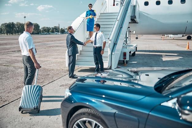 Elegante uomo d'affari che arriva in aereo in auto con autista e stringe la mano al pilota prima del volo