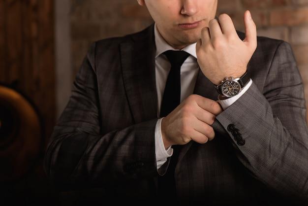 Uomo d'affari elegante che corregge i suoi gemelli e manica.
