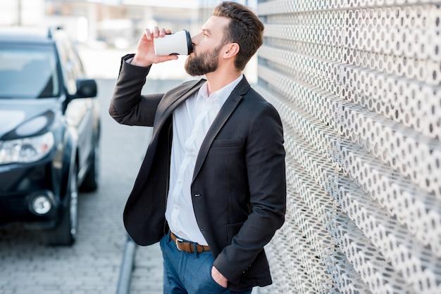 Elegante uomo d'affari in piedi con il caffè per andare vicino alla macchina alla moderna stazione di servizio