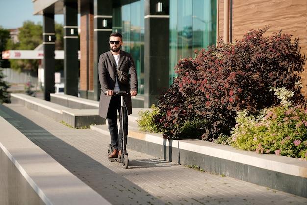 Elegante uomo d'affari in occhiali da sole in movimento su scooter elettrico lungo cespugli che crescono dal moderno centro ufficio mentre si va a lavorare