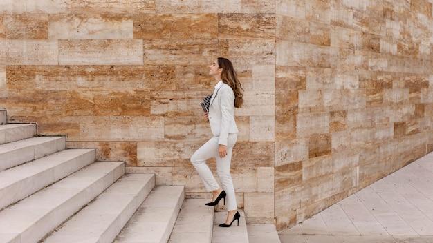 Elegante imprenditrice salire le scale all'aperto