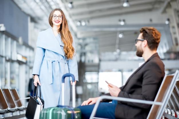 Elegante donna d'affari nel cappotto che incontra l'uomo d'affari nella sala d'attesa dell'aeroporto