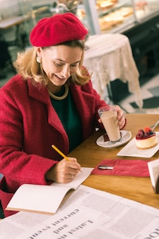 Elegante imprenditrice. donna di affari matura elegante che fa alcune note che si siedono nel forno e che bevono caffè