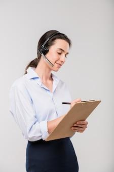 Donna di affari elegante in cuffia avricolare che prende le note nel documento mentre consulta i clienti sul telefono