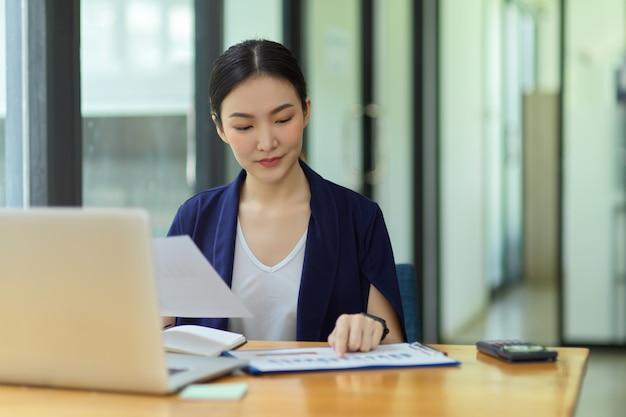 Elegante donna d'affari che utilizza software aziendale per l'analisi dei dati e la gestione dei progetti tramite laptop