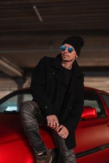 Un bell'uomo elegante e casual con eleganti occhiali da sole blu in un cappotto nero alla moda con un cappello si siede su un'auto rossa per strada