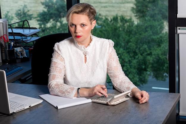 Elegante contabile bionda caucasica donna d'affari seduto al tavolo in ufficio utilizza una calcolatrice e scrive i dati in un taccuino. la donna in camicia bianca e capelli alla moda prende appunti su un taccuino.