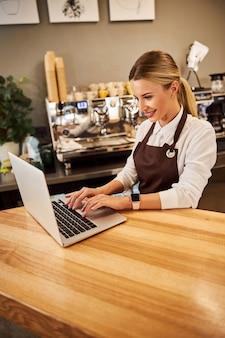Elegante amministrazione femminile caucasica del caffè guardando lo schermo del computer