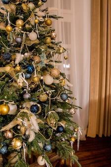 L'elegante albero di natale è decorato per le vacanze con palline gialle, oro, blu, lucide e giocattoli