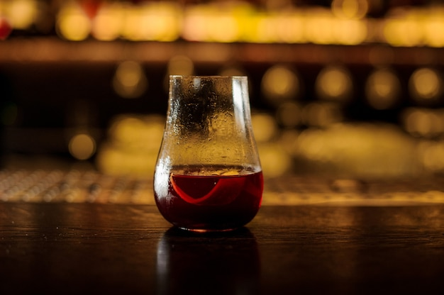 Elegante bicchiere da cocktail riempito con cocktail rosso dolce amaro fresco sulla barra contro luci dorate