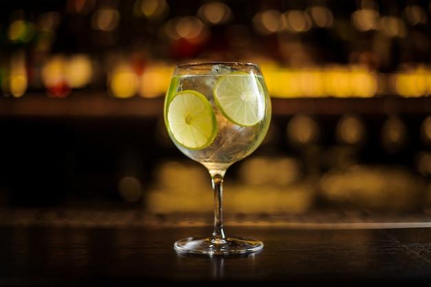 Elegante bicchiere da cocktail con cocktail di agrumi freschi e dolci con fettine di lime in controluce