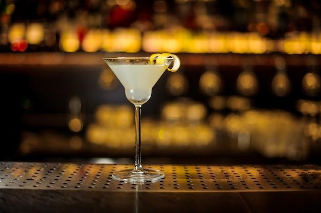 Elegante bicchiere da cocktail con cocktail fresco aspro e dolce decorato con scorze d'arancia contro luci dorate