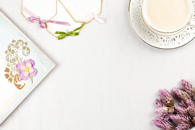 Elegante tazza di caffè, taccuino, etichette di carta e fiori distesi. sfondo femminile in colori pastello. vista dall'alto