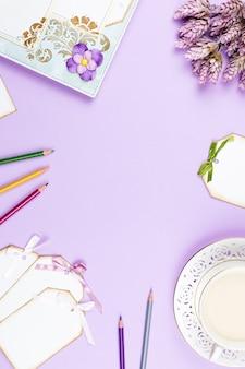Elegante tazza di caffè, quaderno e fogli di carta distesi. sfondo femminile in colori pastello. vista dall'alto