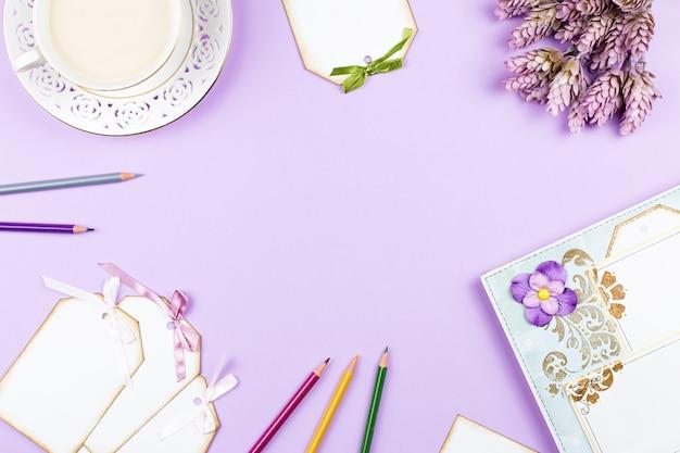 Elegante tazza di caffè, quaderno e fogli di carta distesi. sfondo femminile in colori pastello.