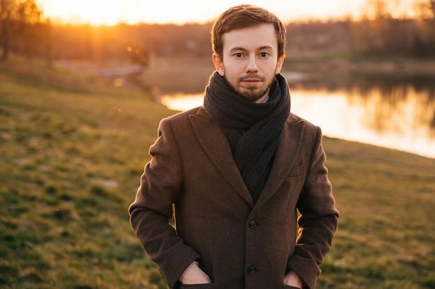 Elegante uomo fiducioso in abiti alla moda in posa nella foresta. caldi colori del tramonto.